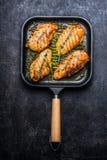 Piec kurczak pierś w grill niecce z świeżymi ziele i pikantność na ciemnym nieociosanym tle obrazy stock