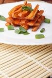 Piec marchewki z zielonymi cebulami na białym talerzu obrazy royalty free