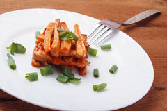 Piec marchewki z zielonymi cebulami na białym talerzu Zdjęcie Stock