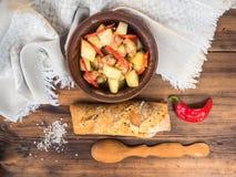 Piec mięso z grulami, chlebem, solą i pieprzem na tle, drewniany stół i prostacki płótno nadal wiejskiego życia obrazy royalty free