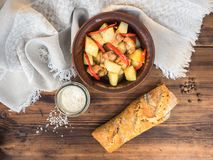 Piec mięso z grulami, chlebem, solą i pikantność na tle, drewniany stół i prostacki płótno Pieczone grule w a fotografia royalty free