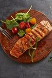 Piec na grillu łosoś z szpinakami i czereśniowymi pomidorami obrazy royalty free
