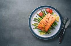 Piec na grillu łosoś garnirujący z zielonym asparagusem i pomidorami Obrazy Royalty Free