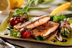 Piec na grillu łosoś z warzywami słuzyć na zieleń kamienia talerzu na drewnianym stole obrazy stock