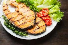 Piec na grillu łososiowy stek słuzyć z piec na grillu pomidorami, sałatka, cytryna pokrajać, pieprzy ziarna, rozmaryny, pietruszk Fotografia Royalty Free