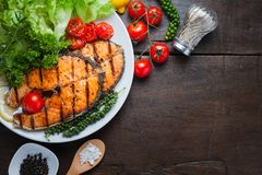 Piec na grillu łososiowy stek słuzyć z piec na grillu pomidorami, sałatka, cytryna pokrajać, pieprzy ziarna, rozmaryny, pietruszk Zdjęcie Stock