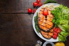 Piec na grillu łososiowy stek słuzyć z piec na grillu pomidorami, sałatka, cytryna pokrajać, pieprzy ziarna, rozmaryny, pietruszk Obrazy Stock
