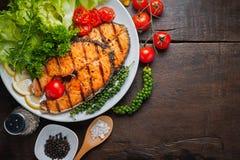 Piec na grillu łososiowy stek słuzyć z piec na grillu pomidorami, sałatka, cytryna pokrajać, pieprzy ziarna, rozmaryny, pietruszk Zdjęcia Stock