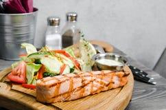 Piec na grillu łososiowy stek z winnika kumberlandem i świeżymi warzywami słuzyć na drewnianym stole przy restauracją Popielaty t Zdjęcie Royalty Free
