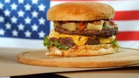 Piec na grillu Amerykański wołowina hamburger z sałatą, ser, cebula słuzyć na kawałkach wiruje na drewnianym kontuarze brązu papi zbiory