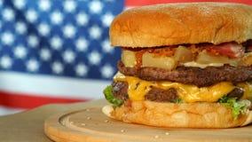 Piec na grillu Amerykański wołowina hamburger z sałatą, ser, cebula słuzyć na kawałkach wiruje na drewnianym kontuarze brązu papi zbiory wideo