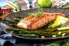 Piec na grillu asparagusy na drewnianym stole i łosoś zamykamy w górę zdjęcia royalty free