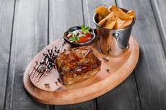 Piec na grillu beaf stek z kumberlandem i grulami smaży w wiadrze na drewnianej tnącej desce Zdjęcia Royalty Free