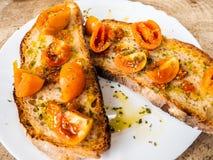 Piec na grillu chlebowy bruschetta z Włoskimi pomidorami, kolorem, bardzo dobry, pomarańczowymi, i trwać, przyprawiam z oliwą z o obraz stock