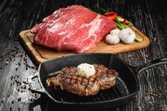 Piec na grillu Czarny Angus stek na grilla żelaza niecce na drewnianym czarnym tle z surowym fotografia stock