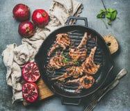 Piec na grillu jagnięcy mięso kotleciki słuzyć z świeżymi granatowami, popielaty tło obraz stock