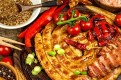 Piec na grillu kiełbasy spirala słuzyć na nieociosanego round tnącej desce z musztardą grill domowej roboty Ogrodowy przyjęcie ka zdjęcia royalty free