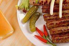 Piec na grillu kiełbasy z warzywami na białym talerzu Zdjęcia Stock