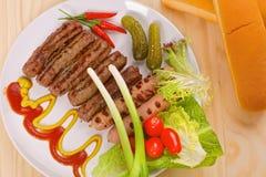 Piec na grillu kiełbasy z warzywami na białym talerzu Zdjęcie Royalty Free