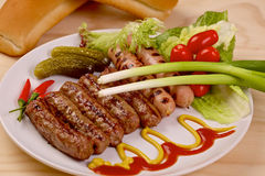 Piec na grillu kiełbasy z warzywami na białym talerzu Fotografia Stock