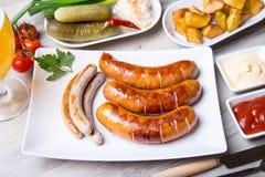 Piec na grillu kiełbasy z grulami ogórki i sauerkraut, z dwa kumberlandami zdjęcie stock