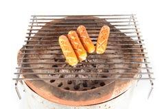 Piec na grillu kiełbasa nad gorącym grilla grillem Obrazy Stock