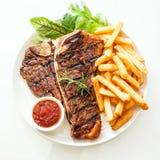 Piec na grillu kość stek przyprawiający z rozmarynami Obrazy Stock