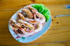 Piec na grillu krewetki na błękitnym naczyniu, umieszczającym na drewno stole Owoce morza menu Zdjęcie Royalty Free