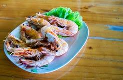 Piec na grillu krewetki na błękitnym naczyniu, umieszczającym na drewno stole Owoce morza menu Fotografia Royalty Free
