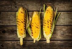 Piec na grillu kukurydzani cobs na rocznika drewna tle Zdjęcie Stock