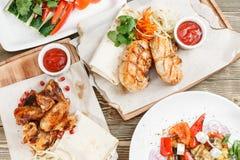 Piec na grillu kurczaków skrzydła i pierś Słuzyć na drewnianej desce na nieociosanym stole Grill restauraci menu, serie Zdjęcia Royalty Free