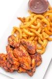 Piec na grillu kurczaków skrzydła z francuzem smażą pomidorowego kumberland na bielu talerzu Obrazy Royalty Free