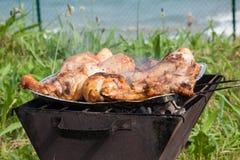 Piec na grillu kurczaków uda na płomiennym grillu. Zdjęcia Stock