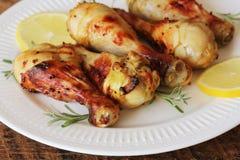 Piec na grillu kurczak nogi z musztardą na drewnianym stole słuzyć na bielu talerzu z rozmarynami BBQ gościa restauracji tło Zdjęcia Stock