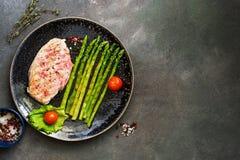 Piec na grillu kurczak polędwicowy w talerzu z asparagusem, pomidorem i pikantność na ciemnym tle, Odgórny widok, kopii przestrze obrazy royalty free