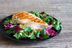 Piec na grillu kurczak polędwicowy z mieszaną sałatką na czarnym talerzu Zdjęcia Royalty Free