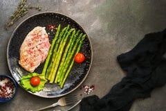 Piec na grillu kurczak pol?dwicowy, szparagowy, pomidorowy, pikantno?? na zmroku - szary t?o Odg?rny widok, mieszkanie nieatutowy zdjęcie stock