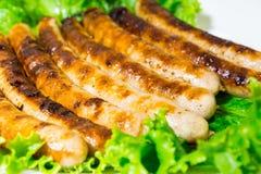 Piec na grillu Niemieckie kiełbasy na grillu z korzennym chili pieprzem Kiełbasy kłaść out na sałata liściach zdjęcia royalty free