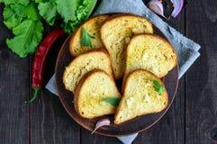 Piec na grillu plasterki biały chleb z czosnkiem i ziele na ciemnym drewnianym tle Obraz Royalty Free