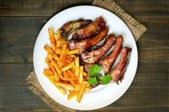 Piec na grillu pokrajać wieprzowina ziobro i francuzów dłoniaki obraz royalty free