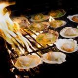 Piec na grillu przegrzebki nakrywający z masłem, czosnkiem i pietruszką na flami, Obraz Royalty Free