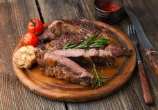Piec na grillu ribeye stek wykładał marmurem mięso z solą, rozmarynami i czosnkiem, Zdjęcie Stock