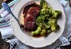 Piec na grillu ribeye stek z gotowanymi brokułami w oliwa z oliwek i morze soli obraz royalty free