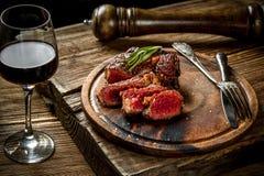 Piec na grillu ribeye wołowiny stek z czerwonym winem, ziele i pikantność na drewnianym stole, obraz royalty free