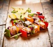 Piec na grillu skewers łosoś i warzywa na drewnianym stole Obraz Stock