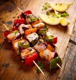 Piec na grillu skewers łosoś i warzywa na drewnianym wieśniaka stole Zdjęcia Royalty Free