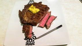 Piec na grillu stek, gotujący środek z beurre kawiarnią de Paryż i bluetooth termometrem na górze talerza, obraz stock