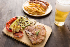 Piec na grillu stek z sałatką, piwo i francuz smaży kiełbasę na wo Zdjęcie Stock
