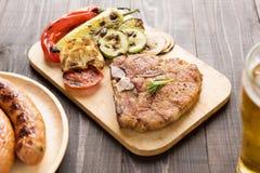 Piec na grillu stek z sałatką, piwo i francuz smaży kiełbasę na wo Obrazy Royalty Free