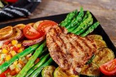 Piec na grillu stki, grula i asparagus na czarnym talerzu, fotografia stock